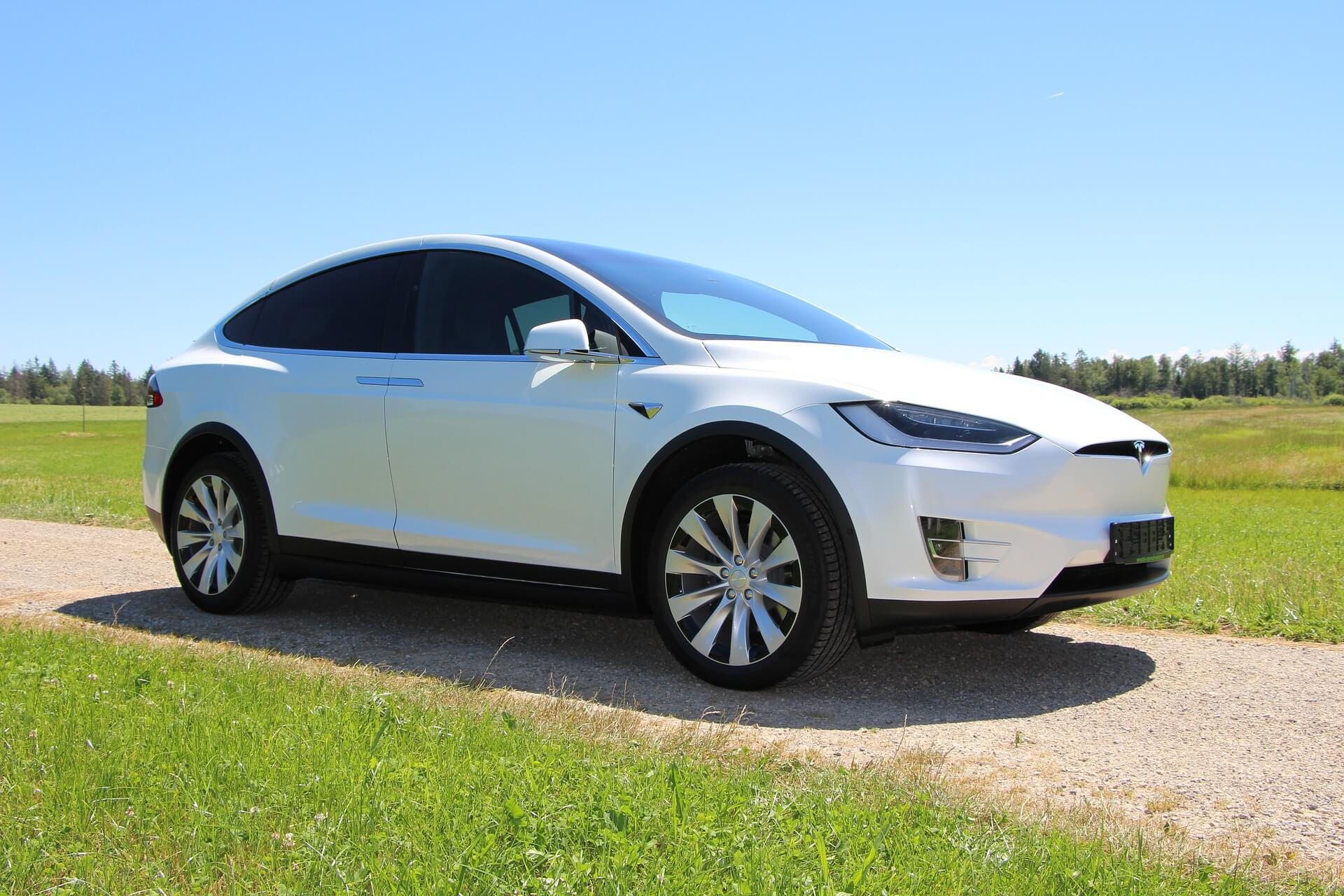 A white Tesla Model X SUV parked on a path with a grassy field background. Segreve & Hall can provide your Tesla with car insurance in North Andover, MA.